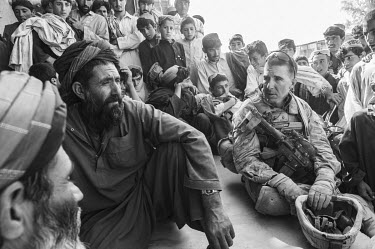 A US Marine commander talks to Afghan locals at the Safar Bazaar.