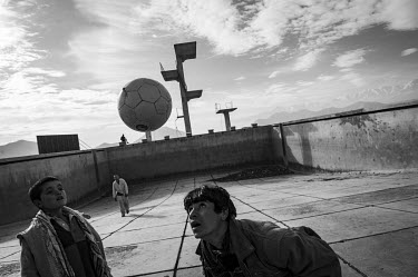 Boys play football in an empty swimming pool built during the Soviet occupation.