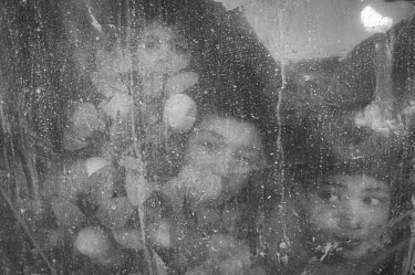 Children looking through a window stained with dust.