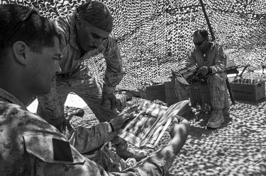 US marines read magazines while on a break from a patrol.