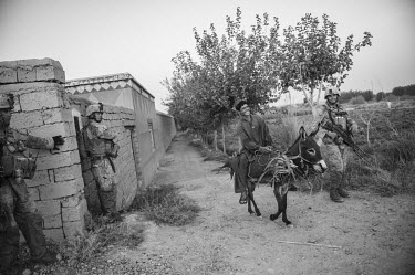 A young man on a donkey laughs as he talks with US marines who are conducting a security patrol.