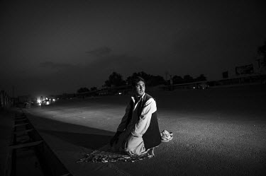 A man prays at the roadside as night falls.