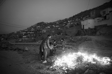 A man tends a fire as a group of children, illuminated by the flames stand beside him.