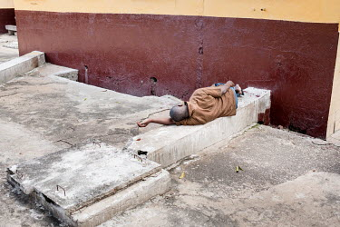 A patient lies on a concrete casing outside at Accra Psychiatric Hospital has four psychiatrists. In 2018 they saw 27,000 patients and admitted 819. They have 19 wards, 7 female, 11 male and one child...