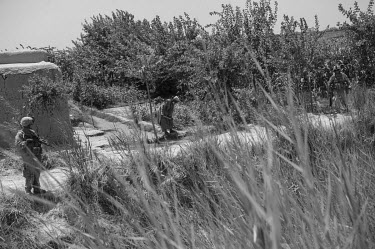 US Marines conduct a patrol as a farmer tends to his crops.