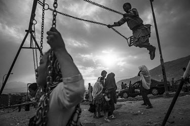 Children playing on swings as they enjoy their weekend at a park.