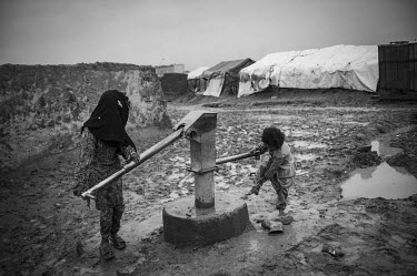 Children pump water at an IDP camp for people who have come, primarily from Helmand province, to the capital city.