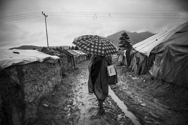 A man walking through mud beneath an umbrella inside a camp for displaced people, who are primarily from Helmand.