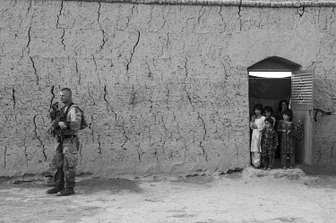 A US Marine stands guard while a group of children look on from the doorway of a house.