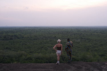 Karin Ostertag and Dassi Bah, a Vodoun (Voodoo) adept, looking out over the Tobe protected forest. Some 350 hectares in area, the forest had been severely degraded by agriculture. Over the last 35 yea...