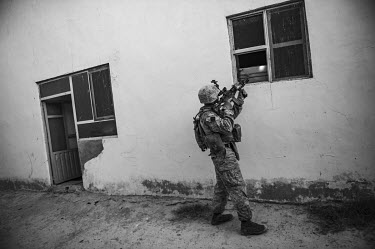 A US marine points his rifle a the window of a house while conducting a security patrol.