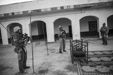 US marines stand beside a child sleeping in a cot in the courtyard of a house where they are conducting a security patrol.