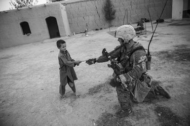 A US Marine gives a bar of chocolate to a boy during a security patrol.