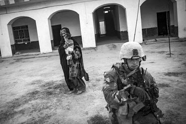A woman and her baby look on as a US marine checks a compound as he participates in a security patrol.
