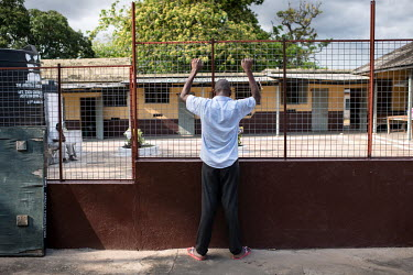 A patient stands at a fence in the grounds at Accra Psychiatric Hospital has four psychiatrists. In 2018 they saw 27,000 patients and admitted 819. They have 19 wards, 7 female, 11 male and one childr...