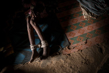 A patient whose ankles are shackled with rope and crepe bandages lies on a mat in a small dark cell at the Emmanuel Rehabilitation Centre for Mentally Ill People which is run by Miss Mojisola Adeniyi....