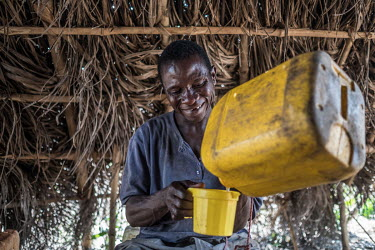 Palm wine tapper Tamba Conteh pours himself a cup of palm wine during a day's work outside Freetown. The drink, known locally as 'poyo', ferments naturally, becoming stronger in taste and alcohol cont...