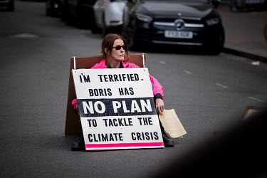 A lone woman climate protestor sits in the middle of Abbeyville Road in Clapham during an Extinction Rebellion 'Rebellion of One' action.
