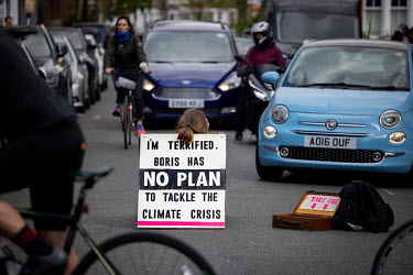 A lone woman climate protestor blocks traffic by sitting in the middle of Abbeyville Road in Clapham taking part in an Extinction Rebellion 'Rebellion of One' action.