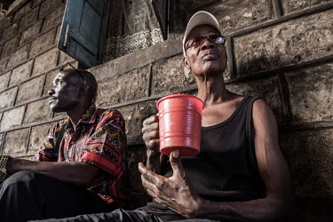 Drinkers enjoy cups of palm wine, or 'poyo', at a speakeasy in central Freetown.