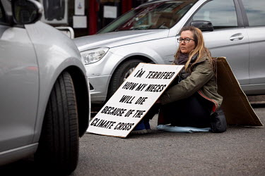 Cars stopped by a lone woman climate protestor sitting in the middle of Abbeyville Road in Clapham during an Extinction Rebellion 'Rebellion of One' action.