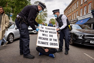 Police arrest a lone woman climate protestor who was blocking traffic by sitting in the middle of Abbeyville Road in Clapham during an Extinction Rebellion 'Rebellion of One' action.