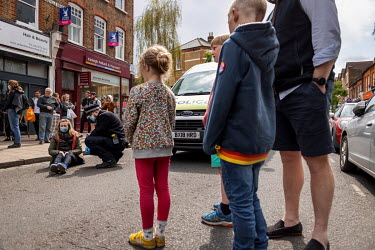 A man and his children look on as police arrest a lone woman climate protestor who was blocking traffic by sitting in the middle of Abbeyville Road in Clapham during an Extinction Rebellion 'Rebellion...