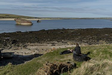 People relax in the sun by Scapa Flow. In the background are the remains of a ship used in the First World War to block the entrance to Scapa Flow to prevent German submarines attacking the British fl...