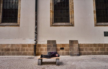 A man sleeps on a bench in front of Bethlehem�Chapel�in the Old Town.