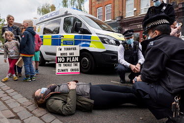 Police try to negotiate with a lone woman climate protestor who was blocking traffic by sitting in the middle of Abbeyville Road in Clapham during an Extinction Rebellion 'Rebellion of One' action.