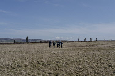 Walkers stop to look at birds next to the Ring of Brodgar, a circle of standing stones that is over 4,000 years old.
