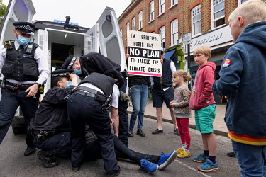 Children look on as police arrest a lone woman climate protestor who was blocking traffic by sitting in the middle of Abbeyville Road in Clapham during an Extinction Rebellion 'Rebellion of One' actio...