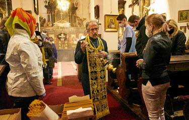 Priest Jan Polansky waves an incense censer during Orthodox Good Friday at St. Ann's Church.