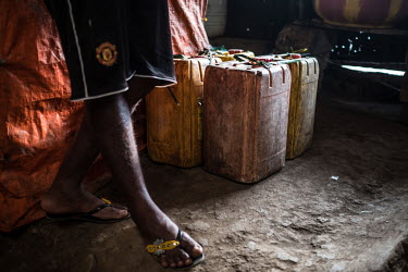 Jerrycans full of palm wine, known locally as 'poyo', stored on the floor of a speakeasy.