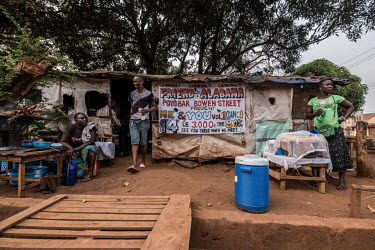 Women selling snacks outside the Friends of Alabama Poyo Bar in eastern Freetown. 'Poyo' bars, selling palm wine, are often little more than shacks of tarpaulin and sticks, but they play an important...