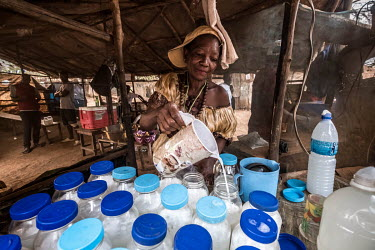Mama-G, the owner of an informal palm wine bar pours out measures of the alcoholic drink made from the sap of palm trees into empty mayonnaise jars for her customers.