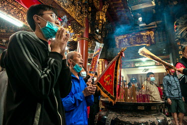 Villagers gather at the 200 year old Taoist (Daoism) Gongtian Temple for a ceremony where temple elders carry an ancient flag from inside the building and place it at the entrance. The temple is dedic...