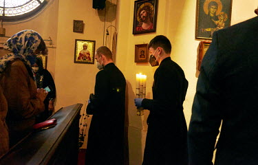 Orthodox priest's assistants carry a Bible and candles during Good Friday at St. Ann's Church.