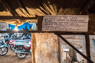 The 'laws of the land' are written on a board in the Friends of Alabama Poyo Bar in eastern Freetown. 'Poyo' bars, selling palm wine, are often little more than shacks of tarpaulin and sticks, but the...