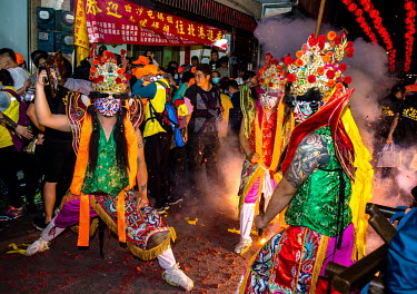 Firecrackers explode in the crowd as performers dressed as temple spirits await the arrival of the palanquin bearing an ancient statue of goddess Mazu in the street outside the 200 year old Taoist (Da...