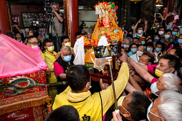 The goddess Mazu deity is carried to the palanquin (left) inside which it will sit for the duration of a 200km pilgrimage starting at the Taoist (Daoism) Gongtian Temple and completed by many follower...