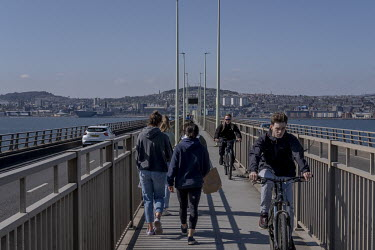 People cross over the Tay river bridge that connects the city to the opposite bank.