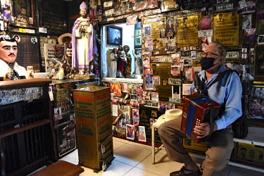 A man plays an accordian in a shop selling Christian and drug cartel related souvenirs including statuettes of Jesus and Joaquin 'El Chapo' Guzman.