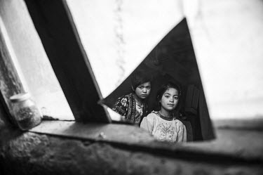 Two girls reflected in a piece of broken mirror propped up against a window in a derelict hut where they live with their family.
