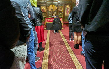 An Orthodox devotee praying on her knees before a picture of Jesus Christ on a Holy Shroud in St. Ann's Church.