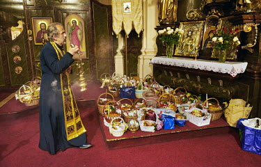 Priest Jan Polansky waves an incense censer over Easter baskets during Orthodox Good Friday at St. Ann's Church.