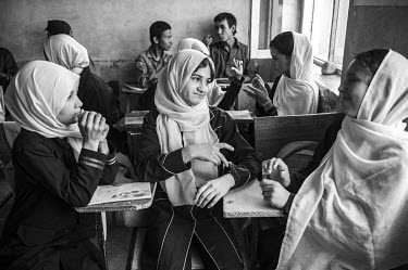 A class of girls using sign language to communicate at a school for the mute.
