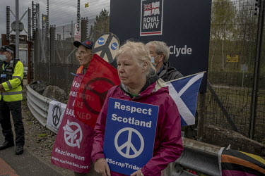 People attend a weekly vigil at the north gate of Faslane naval base where they have gathered to protest against the Trident nuclear submarine stationed there. The Scottish National Party (SNP) has vo...