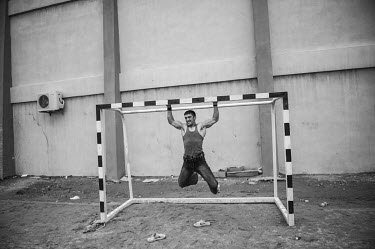 A bodybuilder hangs from a football goals' frame.  Bodybuilding was frowned upon during Taliban rule and the participants had to wear loose fitting trousers and t-shirts during workouts and competitio...