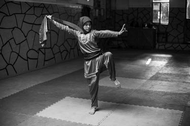 A girl practices martial arts with a sword at a Wushu training club.